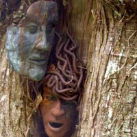'Face en Face (Copper and Steel Faces Peering from Tree sculptures)' by Jason Le Noury