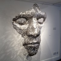 Mask, Wall Hung Faces and Part Heads by sculptor artist Rick Kirby titled: 'Cloud Formation (abstract Outsize Mans Face sxculpture)' in Stainless steel or mild steel coins